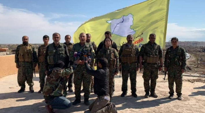 Senior SDF commanders with Al-Baghouz and the organization flag in the background (Furat Post, March 23, 2019).