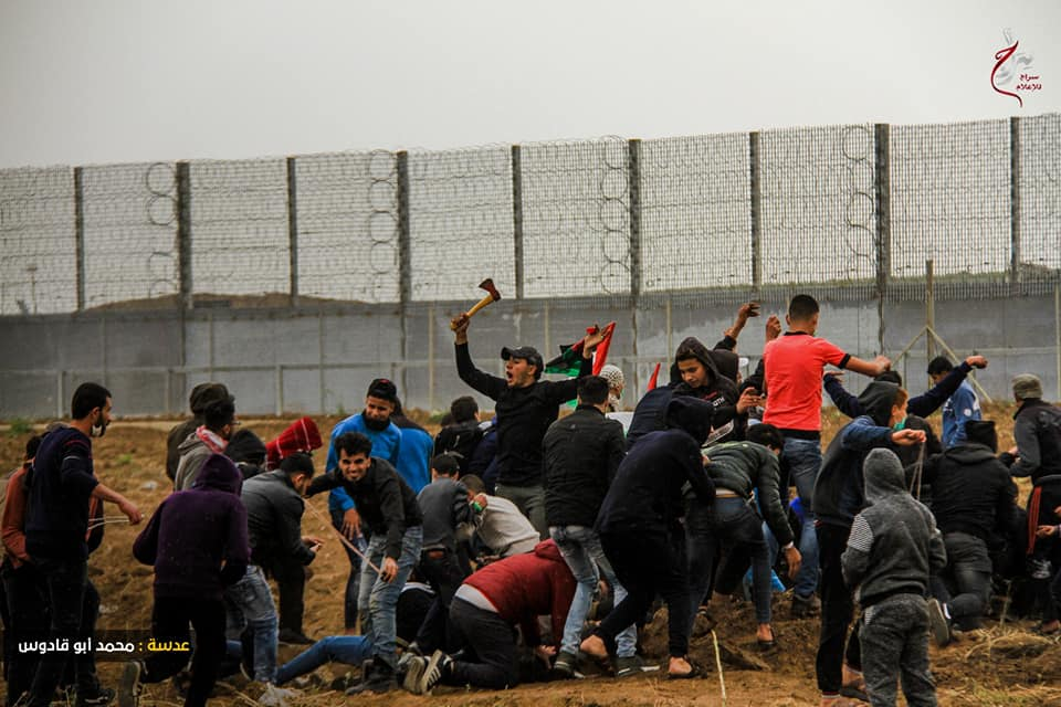 Palestinian rioters near the security fence in the eastern Gaza Strip. One of them is waving an axe (Shehab Facebook page, March 30, 2019).