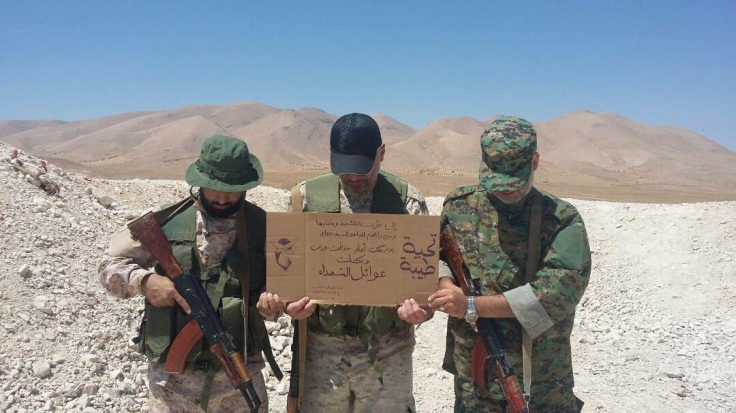 Hezbollah operatives in Syria holding a sign praising the employees of the Martyrs Foundation for their care for the families of the shahids (Facebook)