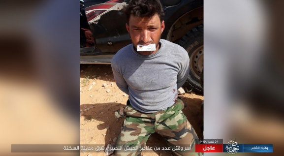Syrian army soldier captured by ISIS east of Al-Sukhnah and subsequently beheaded. He is shown holding an ID card in his mouth (Akhbar al-Muslimeen, April 30, 2019).