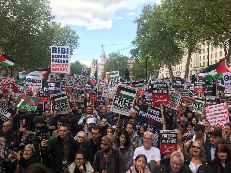 The demonstration in London. On the left senior Hamas figure Zaher Birawi holds an umbrella with the colors of the Palestinian flag (next to the woman in yellow), and left to right, Husam Zomlot, (with the kaffia around his neck) Ahed Tamimi and her father, Bassem (Zaher al-Birawi's Facebook page, May 11, 2019).