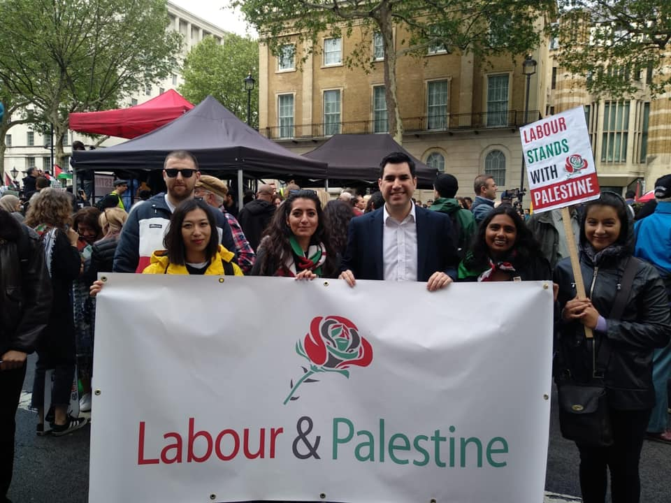 "British Labour Party Richard Burgon at the Nakba Day demonstration, holding a sign showing the Labour Party's support for Palestine (Richard Burgon's Facebook page, May 11, 2019). He said ""Palestine has the right to exist but sadly that is a right that is increasingly threatened … Palestinians should be able to live free from ever expanding settlements on stolen land"" (Guardian, May 10, 2019)."