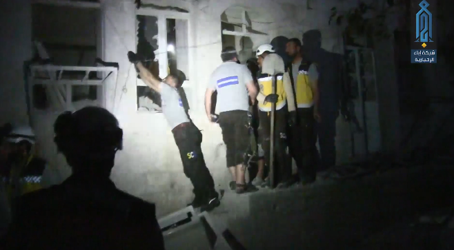 Rescue teams near a building which was hit in central Maarat Nu'man, in the wake of a Russian airstrike.