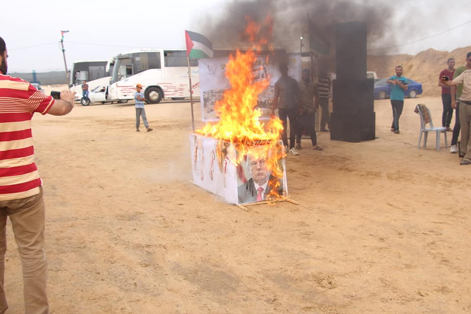 """Burning a """"coffin"""" of the """"deal of the century"""" in the return camp in the central Gaza Strip. The coffin is decorated with a picture of Trump (Supreme National Authority Facebook page, May 31, 2019)."""