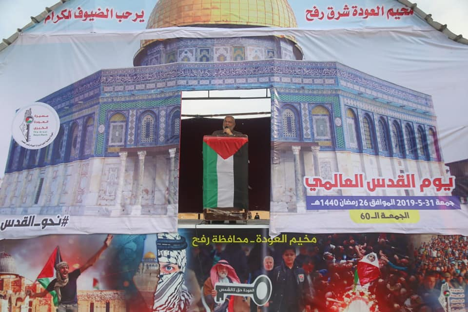 """Ahmed Bahar at the return camp in eastern Rafah. The backdrop is a large picture of the Dome of the Rock with a Palestinian flag and a key symbolizing the [so-called] """"right of return"""" (Facebook page of the Palestinian Legislative Council in the Gaza Strip, May 31, 2019)."""