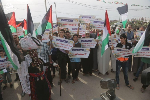 Palestinians participate in activities in eastern Gaza City with signs against the