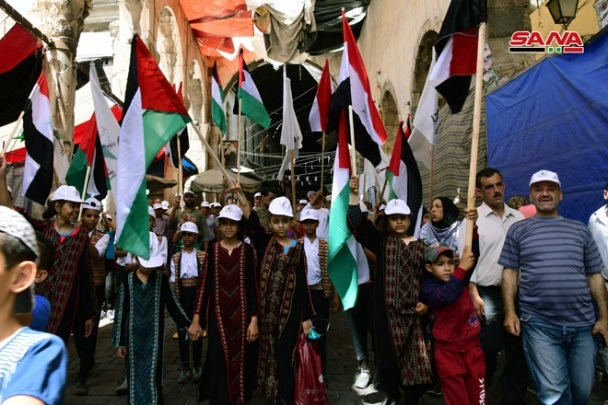 Jerusalem Day marchers in Damascus wave Palestinian and Syrian flags.
