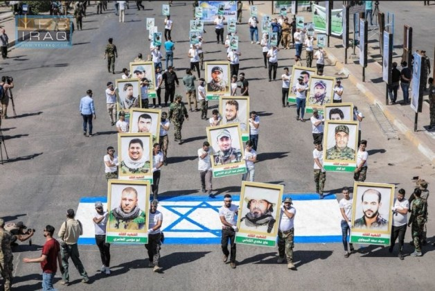 Jerusalem Day marchers carry pictures of shaheeds, and walk on an Israeli flag pained on the road (Yes Iraq website, May 31, 2019).
