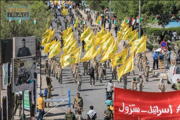 "Jerusalem Day marchers wave flags of the al-Nujaba Movement of the Shi'ite militias, handled by the Iranian Qods Force. Marchers carry a sign reading ""Israel_will disappear."""