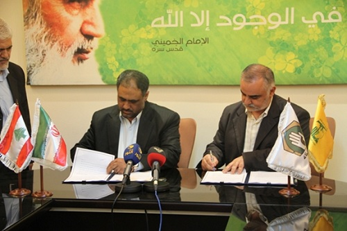 Signing the cooperation agreement between Jihad al-Bina and the Iranian Ministry of Cooperatives, Labor and Social Welfare. On the right, there are flags of Hezbollah and Jihad al-Bina. On the left, there are flags of Iran and Lebanon (Jihad al-Bina website, March 3, 2014).