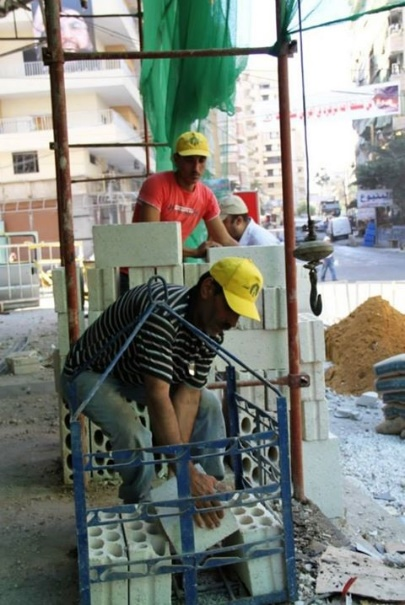 Workers and tractors of Jihad al-Bina repairing the damage caused by the blast in the Al-Ruwais neighborhood of southern Beirut. The flag and hats bearing the emblem of Jihad al-Bina are clearly evident and intended to increase support for Hezbollah among the residents (Jihad al-Bina website, August 27, 2013)