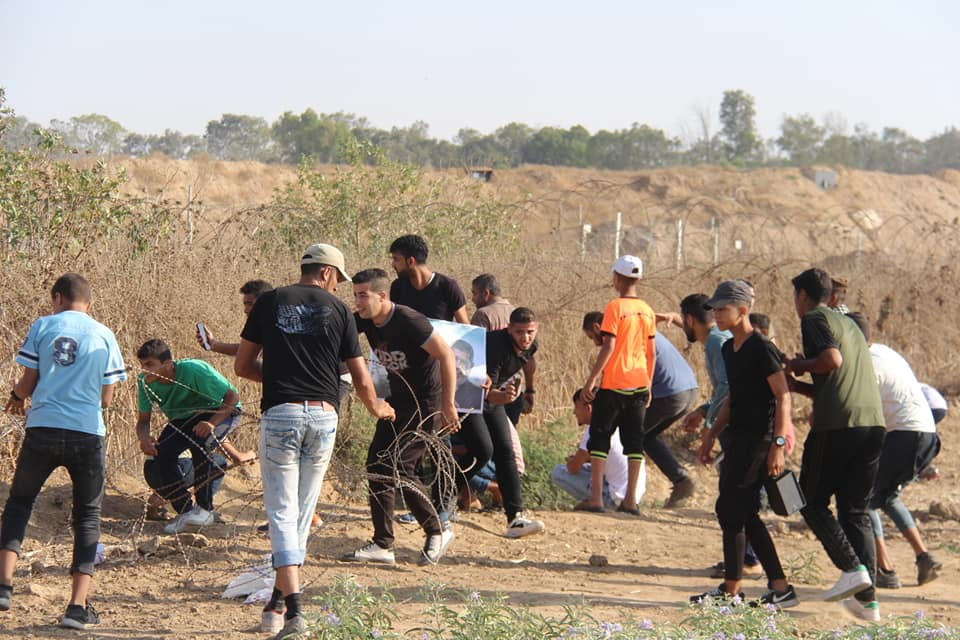Palestinian rioters pull at the barbed wire fence near the security fence in the eastern part of the al-Bureij refugee camp (Supreme National Authority of the Great Return March Facebook page, June 21, 2019).