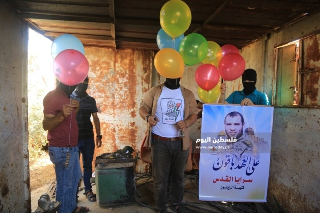 Baraq unit operatives with balloons ready for launching. An operative holds a sign of the Jerusalem Brigades in the al-Zeitoun [neighborhood of Gaza City] (Paltoday, June 27, 2019).