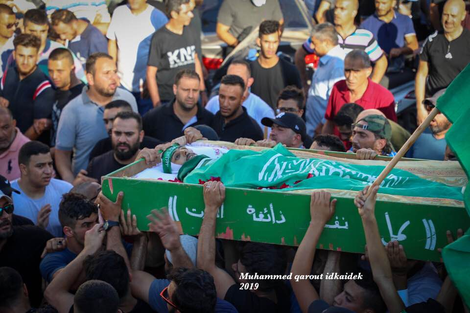 The body of Muhammad A'bied with a Hamas headband and wrapped in a Hamas flag for burial (Facebook page of Jerusalem photojournalist Muhammad Qarout Idkaidek, July 1, 2019).