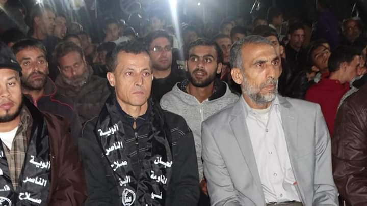 Nihad al-Dahoudi (black shirt) at a PRC military wing memorial service in Khan Yunis. Al-Dahoudi is wearing a scarf bearing the inscription,