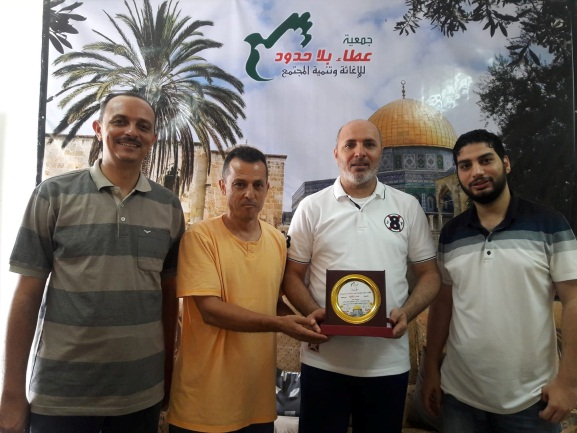 Munzir Shaqliya (second from right) holds a plaque (Generosity Association Facebook page, July 15, 2018).