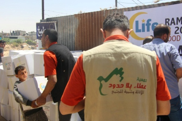 Senior Generosity Association activists stand near packages of food, apparently for distribution during Ramadan. The Life for Relief and Development logo appears on the packages (Generosity Association Facebook page, May 30 2019).