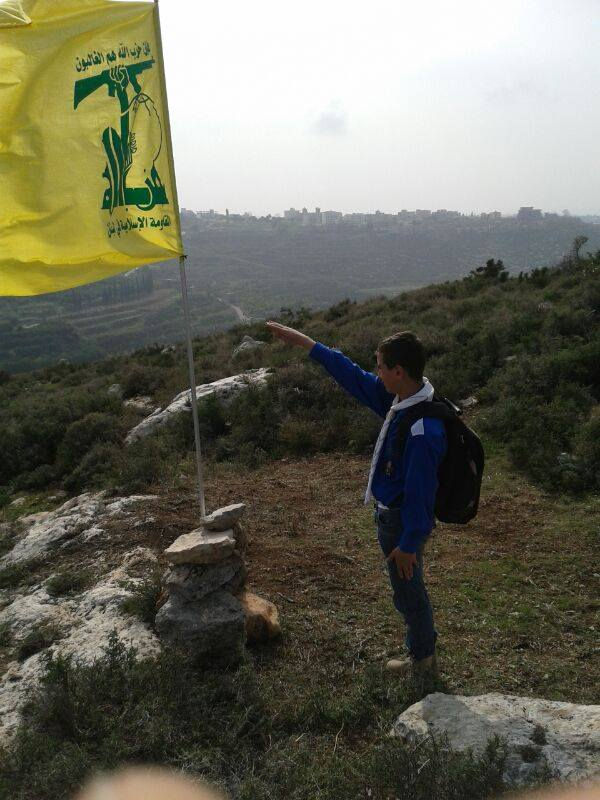 Member of the Imam al-Mahdi Scouts salutes the flag of Hezbollah, apparently during the reenactment of a Hezbollah military activity (Facebook)