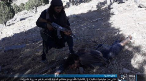 ISIS operative near the body of a Taliban man killed during the attack in the Wadi Hasar area of the Nangarhar Province (Telegram, July 12, 2019).