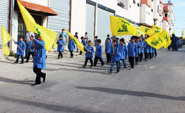 Students of the Al-Mahdi school in Al-Qatrani waving Hezbollah flags and holding photos of shahids as part of the Shahid Day events (Facebook page of Fatima Baalbaki, November 15, 2016)