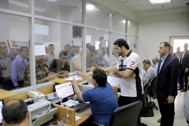 The deputy chairman of the Qatari committee watches the distribution of funds at a post office bank in the Gaza Strip (Facebook page of the Qatari National Committee for the Reconstruction of Gaza, July 22, 2019).