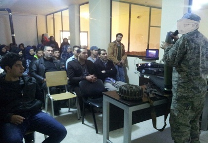Hezbollah fighter explains on various types of weapons during a meeting with students and lecturers in the Al-Massar academic institute in the village of Al-Lubuwwa in the Bekaa Valley (Education Mobilization website, no date)