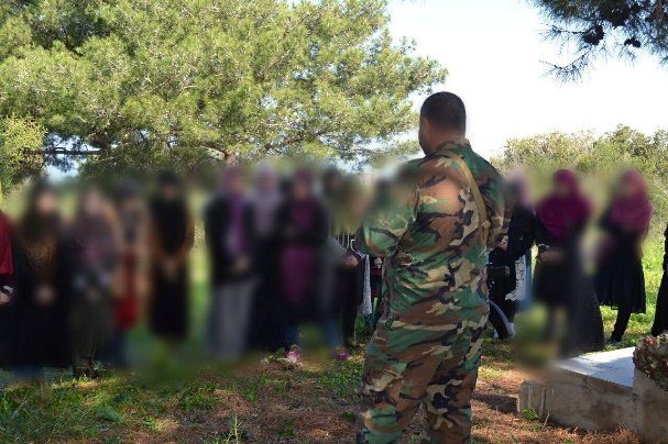 Armed Hezbollah fighter talking to female student members of the Nour Club, an Education Mobilization student cell at LIU (Lebanese International University). The talk took place during a trip organized by the Education Mobilization to the village of Naqoura in southern Lebanon.