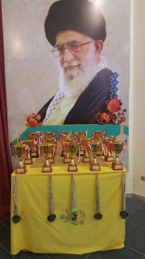 "A martial arts event dedicated to the ""Shahids of the Holy Defense"" (the name used by Hezbollah to refer to its operatives killed in Syria). The event was held in the hall of the Abu al-Fadl sports club (Abu al-Fadl is an important figure in Shiite Islam), in the village of Burj Qallawiyah in southern Lebanon. Photos of Imam Ruhollah Khomeini and Khamenei were prominently displayed at the award ceremony. Khomeini, the Father of the Islamic Revolution in Iran (right) and Iranian leader Ali Khamenei (left) are two figures considered by Hezbollah as the source of legitimacy for its actions."