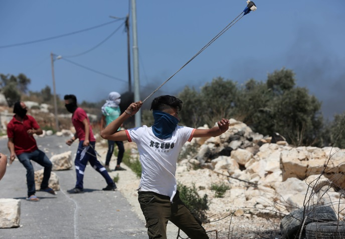 Palestinians throw stones at the Israeli security forces during the weekly riots in Kafr Qaddum (Wafa, July 26, 2019).