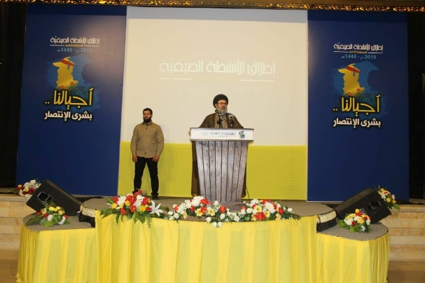 "Chairman of the Executive Council Sayyid Hashem Safi al-Din delivers a speech at the ceremony. The logo designed for the event is visible in the background: A silhouette of a boy, a student and a man wearing a cap decorated with a red band (a sort of a desired ""life cycle"" for a Hezbollah supporter, according to which Hezbollah's civilian infrastructure has been created: from infancy, through studies, to military or civilian activity in the ranks of Hezbollah) (Facebook page of the Rassed network, June 28, 2019)"
