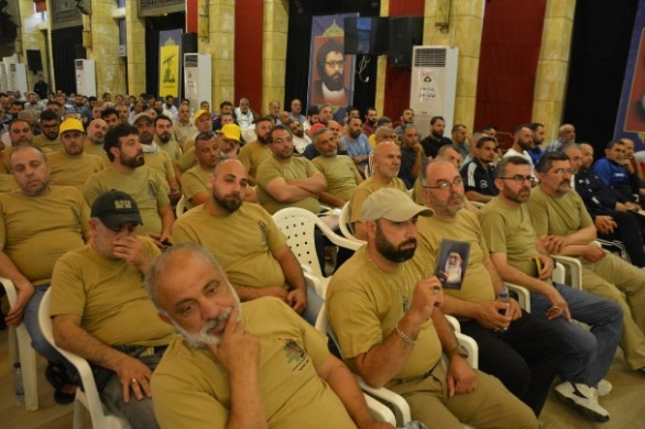 "Representatives of the ""Lebanese Companies of Resistance to the Israeli Occupation"" who attended the ceremony (Facebook page of the Rassed network, June 28, 2019). A poster with the Hezbollah emblem and the picture of Sayyid Abbas Mussawi, Nasrallah's predecessor who met his death in a targeted killing, are visible in the background."