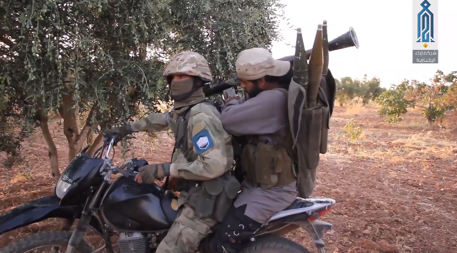 Operatives of the Headquarters for the Liberation of Al-Sham riding a motorcycle before setting out to halt Syrian army attempts to advance towards Tal Tarei.