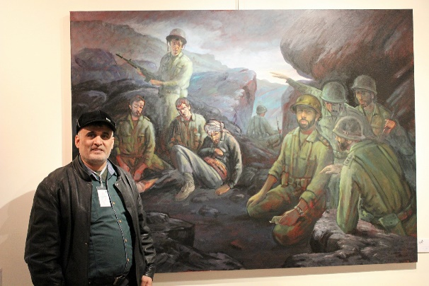 Ahmad Abdallah near one of his paintings showing a scene of the Iran-Iraq War (Ahmad Abdallah's Facebook page)
