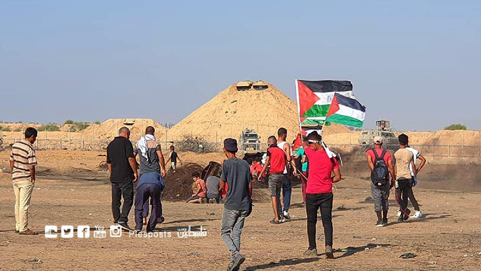 Demonstrators wave Palestinian flags near the security fence in eastern Khan Yunis.
