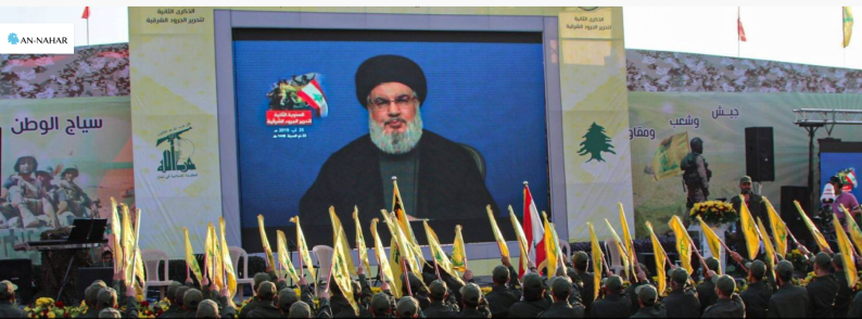 Operatives in uniform carrying Hezbollah and Lebanese flags cheer Nasrallah before his speech.