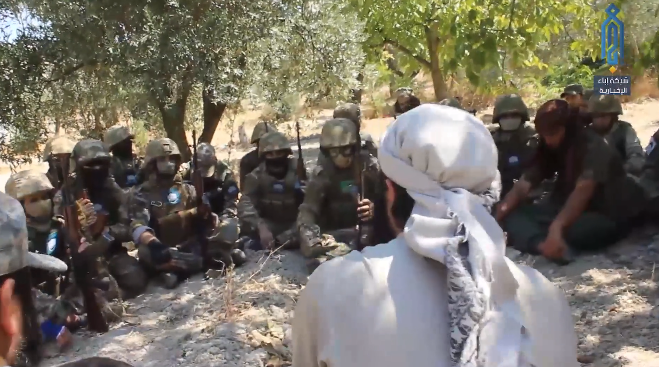 Operatives of the Headquarters for the Liberation of Al-Sham listening to a cleric a short while before setting out to halt a Syrian army attempt to advance towards the hill of Kabanah (Ibaa, August 26, 2019)
