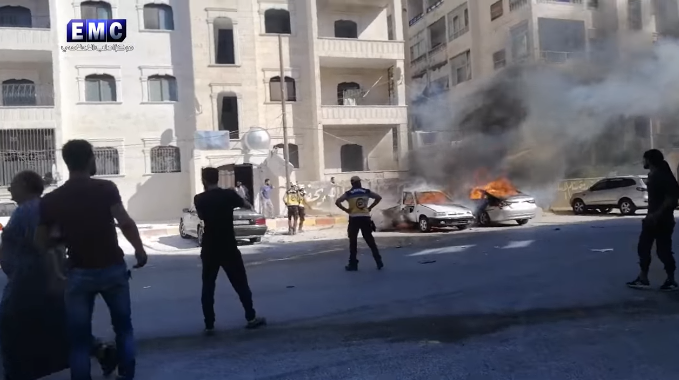 The car of Abu Khaled the Engineer (a white car on the left) on fire after the detonation of the IED (Rebel-affiliated Facebook page Edlib Media Center, August 22, 2019)