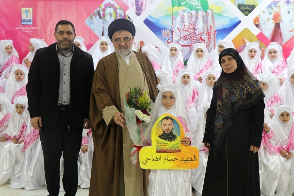Group ceremony of girls coming of age at the Al-Mahdi schools in Mashghara, Kafr Fila and Al-Ahmadiyah. A total of 88 girls coming of age from these schools took part in the ceremony (Facebook page of the Al-Mahdi school in Mashghara, February 20-24, 2019). The girl in the middle is holding a photo of a shahid.