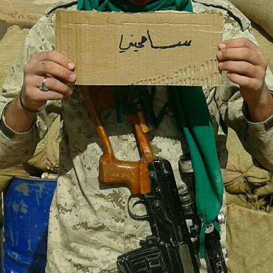 "Operative of Hezbollah's military wing holding a sign that reads, ""Forgive me"" (asking for his mother's forgiveness because he may not return from battle) (Facebook)."