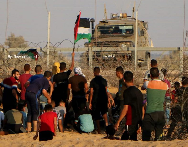 Demonstrators in eastern Rafah wave a Palestinian flag near the security fence and at an IDF vehicle.
