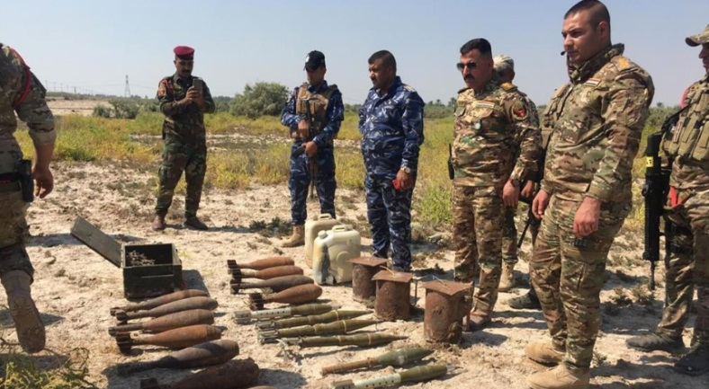 Emergency Response Division commanders standing near the weapon stockpile (Al-Sumaria, September 9, 2019)