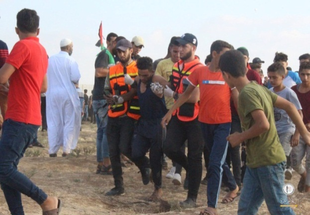 """Ushers in orange vests assisting in the evacuation of a wounded Palestinian in eastern Gaza City (""""Malaka Return Camp"""" Facebook page, September 13, 3019)"""