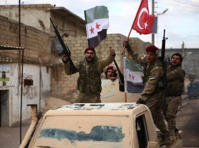 Syrian National Army fighters wave Turkish and Syrian revolutionary flags during