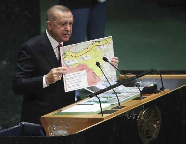 Turkish President Erdogan holds a map of the planned