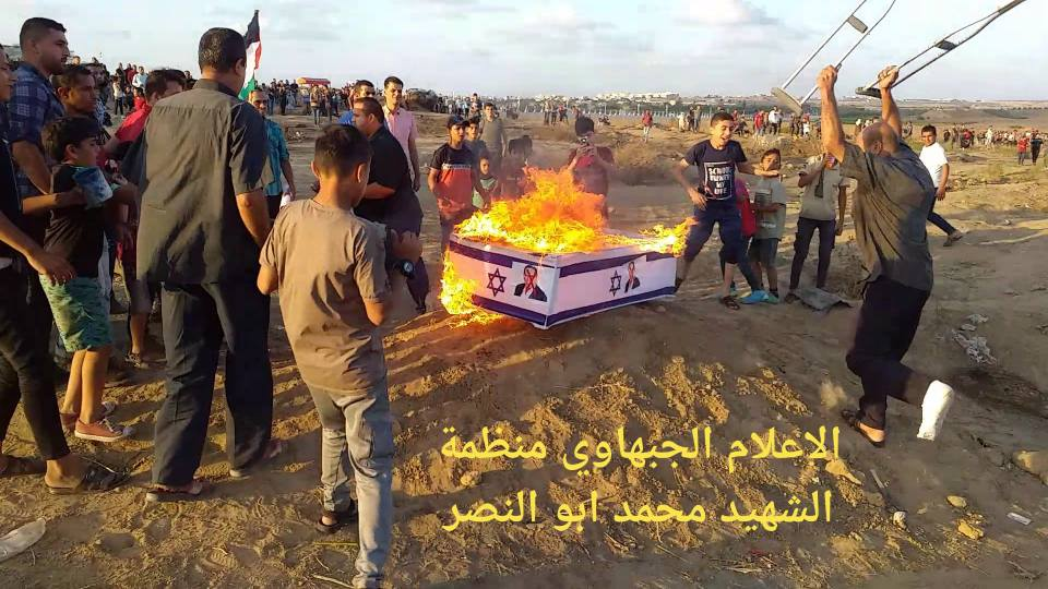 "Rioters in the eastern part of the al-Bureij refugee camp burn a ""coffin"" with a picture of the Rehavam Ze'evi, the late Israeli minister of tourism, to mark the anniversary of his murder by Palestinian terrorists (Abu Wattan's Facebook page, October 18, 2019)."