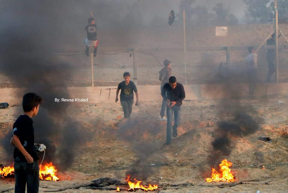 Palestinian rioters climb on the security fence and burn tires in eastern Rafah (Supreme National Authority Facebook page, November 1, 2019).