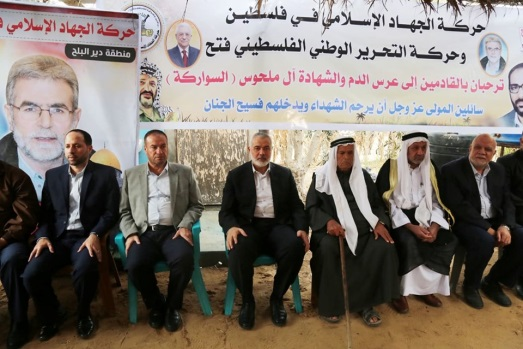 Isma'il Haniyeh, center, in the mourning tent of the Abu Milhous (al-Sawarka) family. Behind him is a PIJ-Fatah sign welcoming the people who come to pay condolence calls.