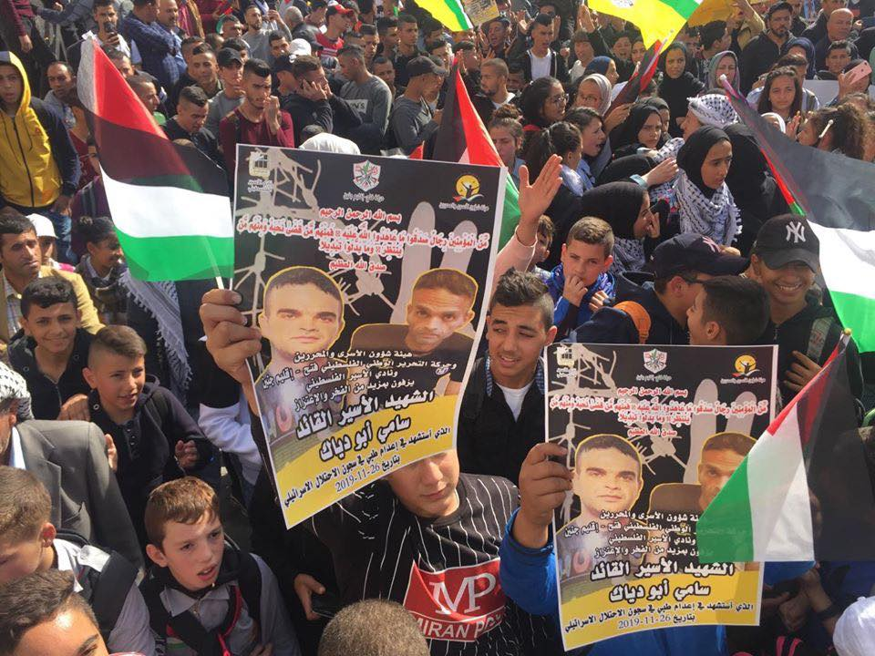Marchers in Jenin hold pictures of security prisoner Sami Abu Diyak, who died in an Israeli prison after an illness on November 26, 2019 (official Fatah Facebook page, November 26, 2019).