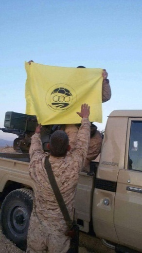 Hezbollah operatives in Syria waving the flag of the Al-Ahed Sport Club on a vehicle with a mounted anti-aircraft gun (Facebook)