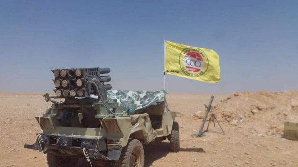 The flag of the Al-Ahed Sport Club on a Hezbollah jeep with a mounted rocket launcher in a Hezbollah outpost, probably in the desert in eastern Syria.